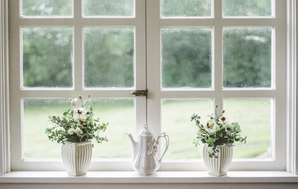 a white window with 2 vases and a jug on the sill