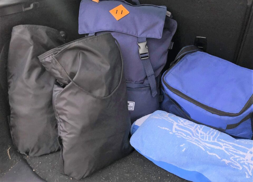 the mozy's tucked up in their pockets to make handy carry bags. They are in the boot with a rucksack, picnic bag and beach towel