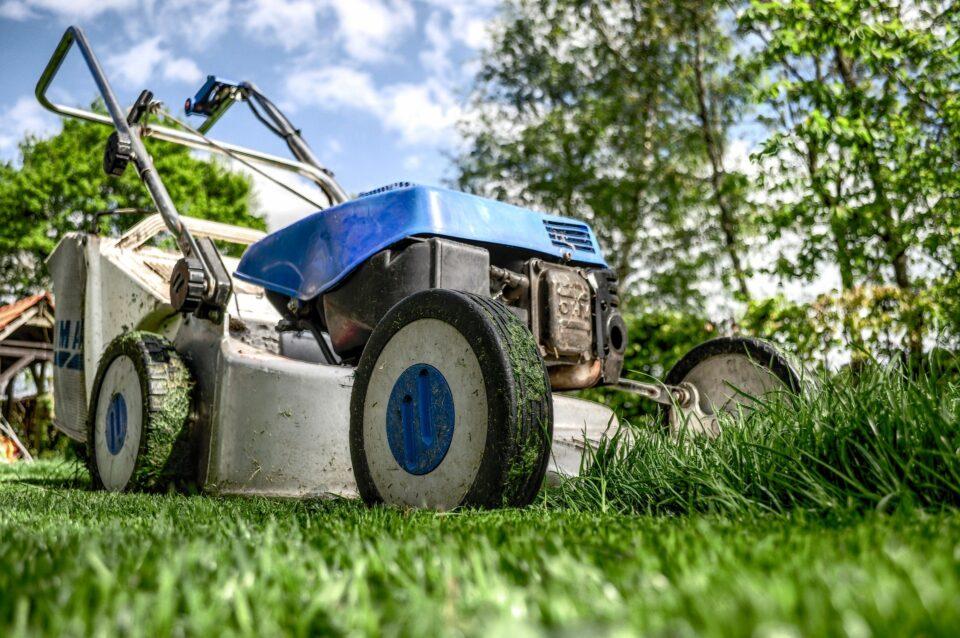 blue lawnmower cutting grass