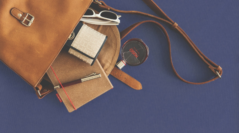 leather handbag on its side with the contents spilled out on a blue background