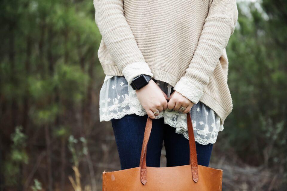 a lady holding a tan leather handbag
