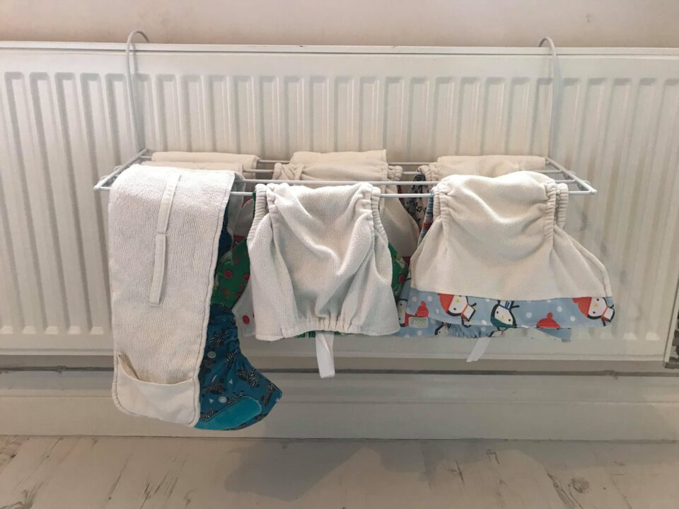 cloth nappies drying on a radiator airer