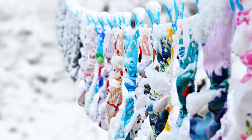 cloth nappies drying on a line in snow on the winter