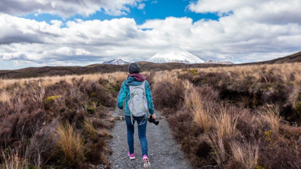 a lady hiking through a bushy field holding a camera