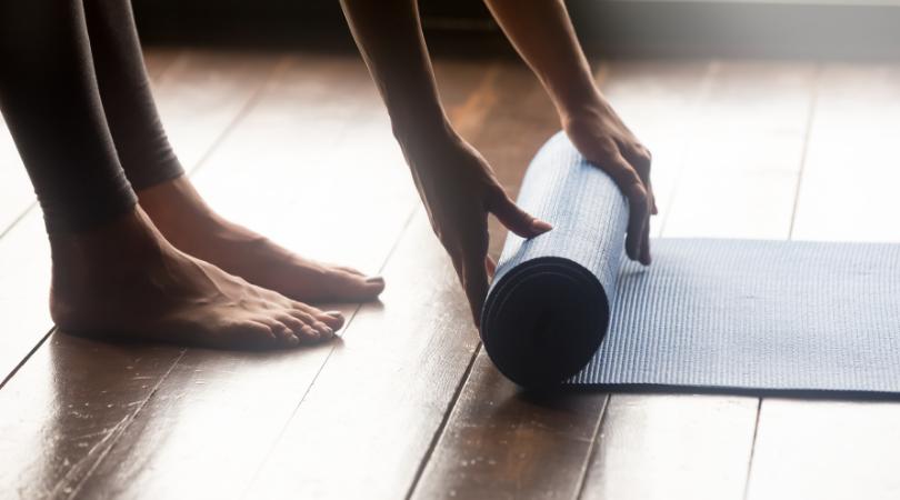 a lady unrolling a yoga mat