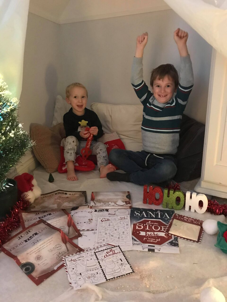 Jake with his arms up in celebration and william cheering whilst sat inside their grotto with their letters