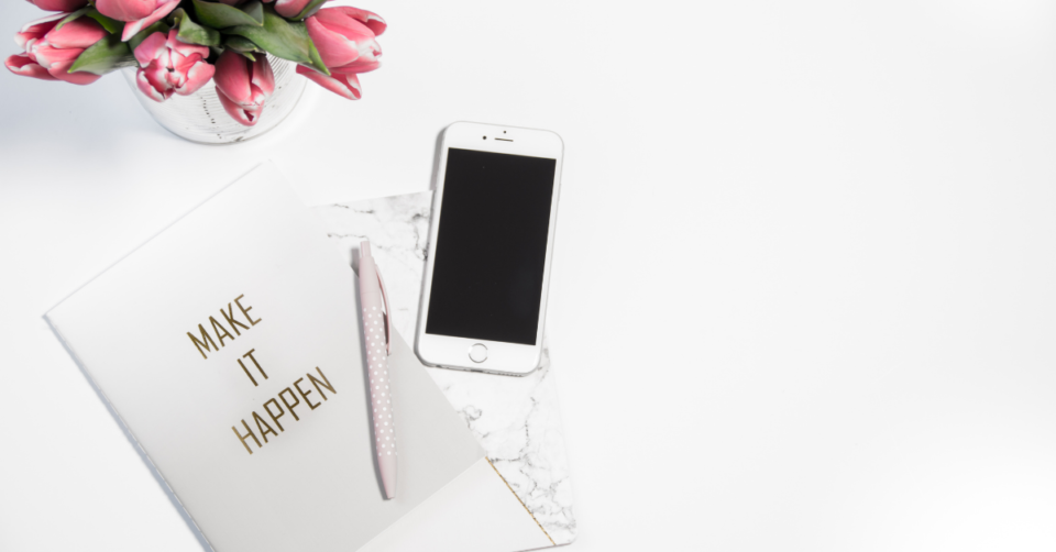 mobile phone next to a pad and pen plus pink roses