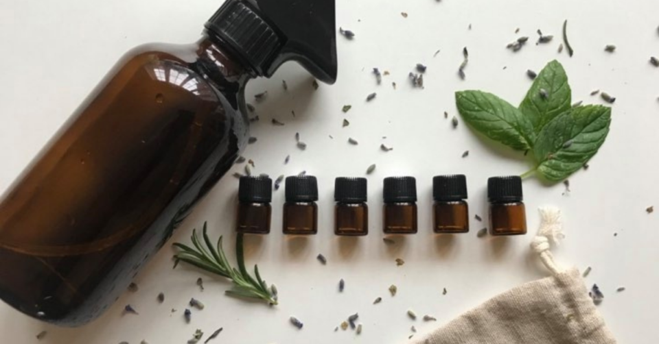 essential oils on a white background next to a spray bottle and with petals and leaves scattered