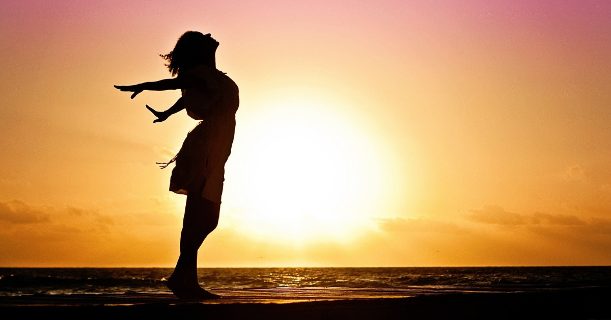 a lady at sunset holding her arms out