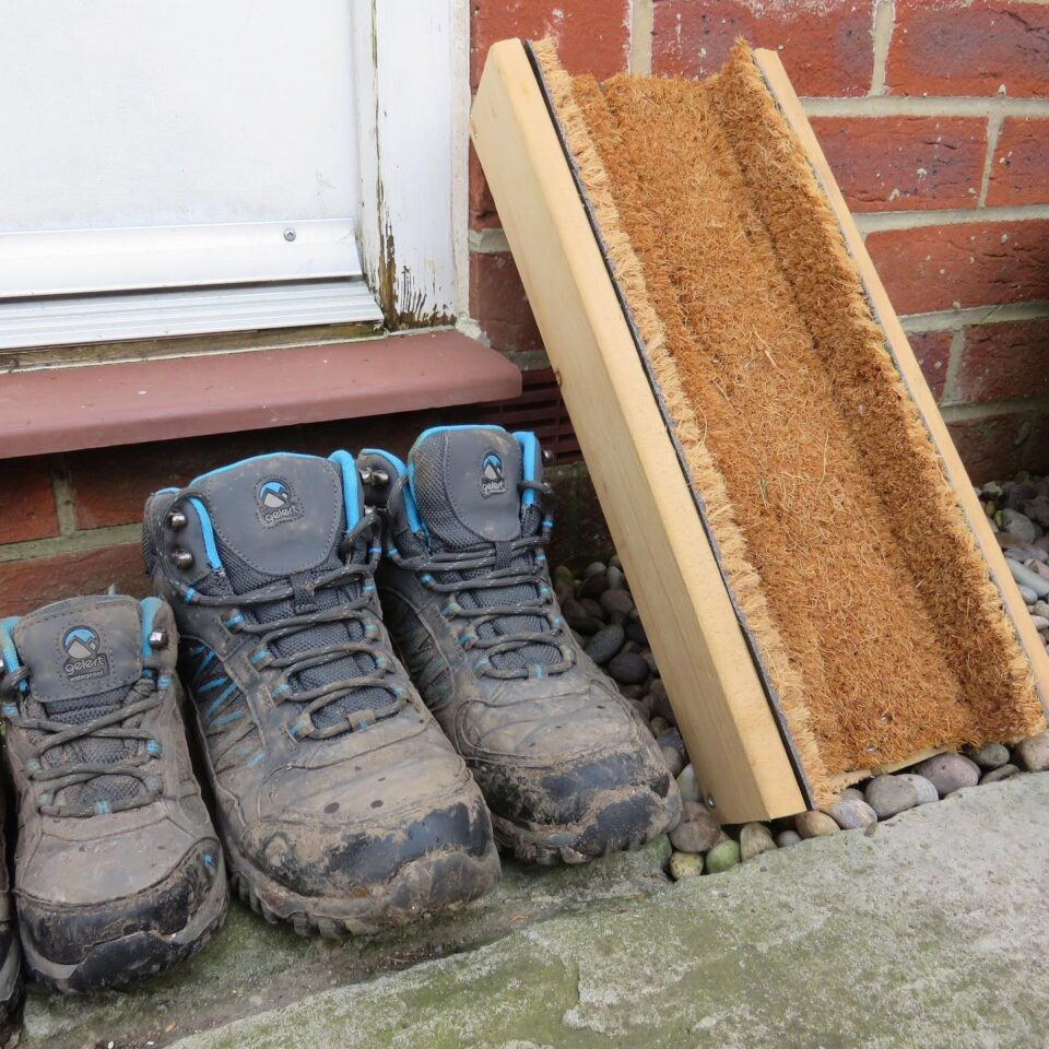 the boot brush outside next to walking boots