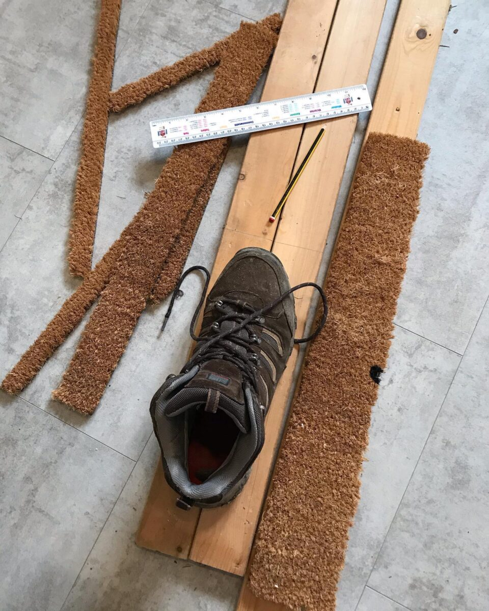 a large boot on planks of wood being measured