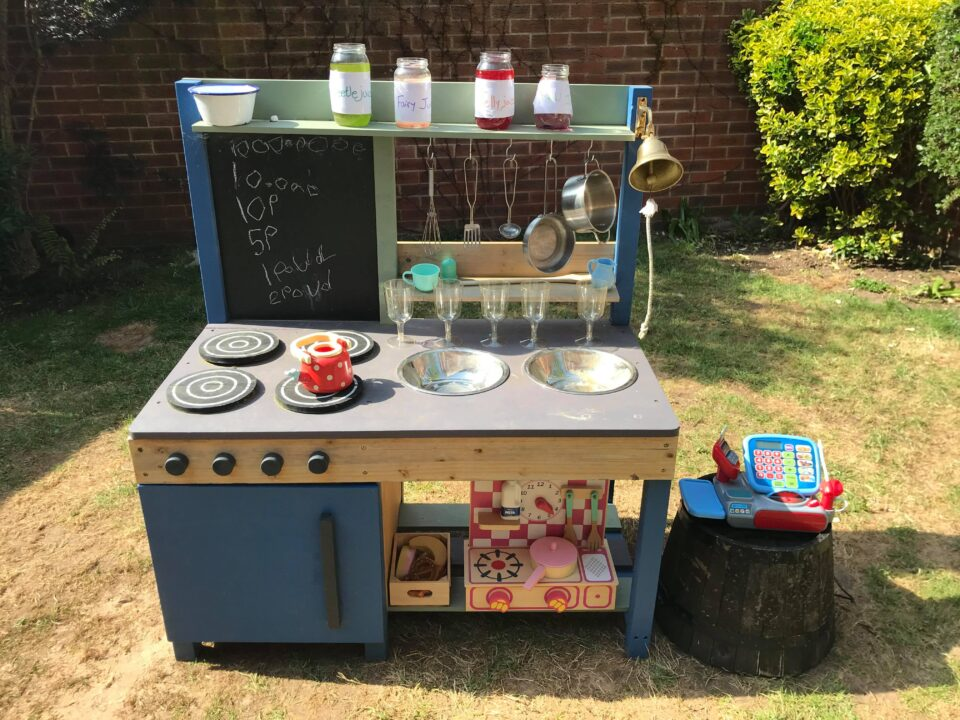 the mud kitchen set up with the fairy juice on it