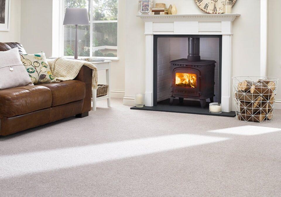 a light living room with cream carpet, log fire and sofa