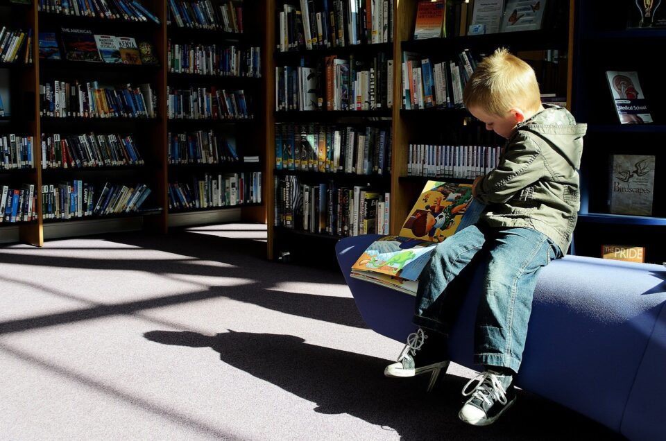 a child sat reading in a library
