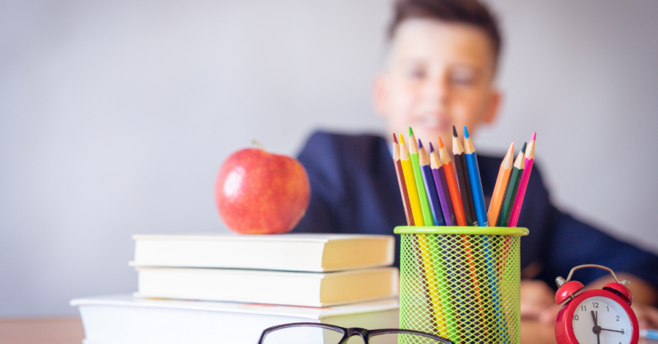 a table of school items with a child sat behind