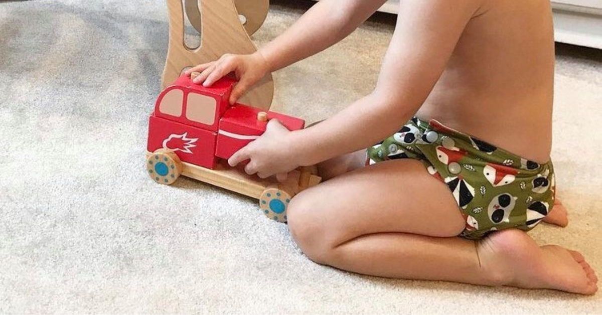 child in a cloth nappy playing with a wooden toy