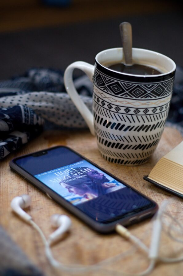 audiobook being listened to on a phone with a cup of coffee sat next to it