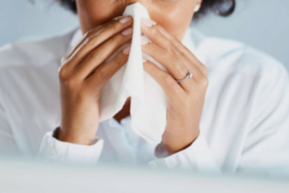 a lady sneezing into a tissue