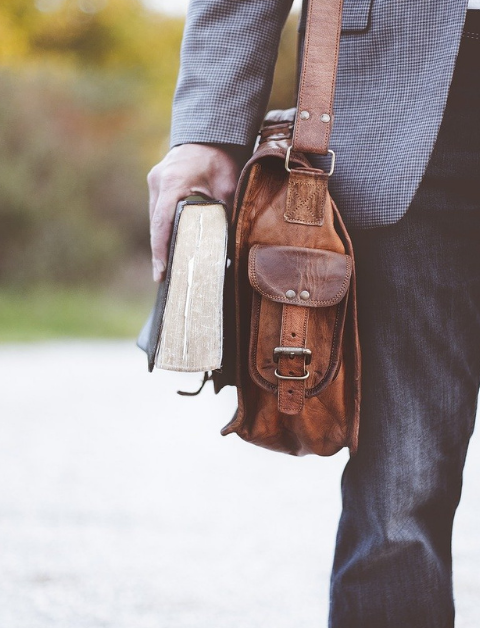 a man with a book bag and holding books