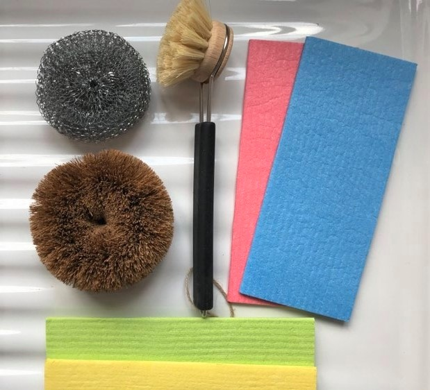 eco-friendly washing up sponges and brushes laying on a white ceramic sink