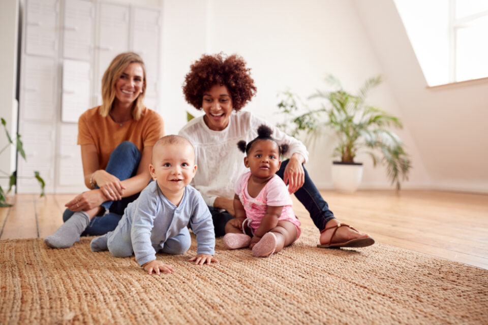 2 mums with 2 babies sitting on the floor smiling