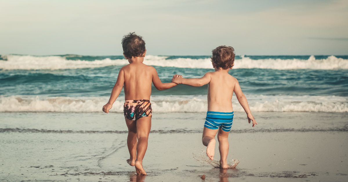 2 boys holding hands on the beach running towards the sea