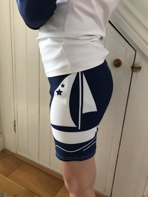 the side of the leg on the swimwear which shows a yacht