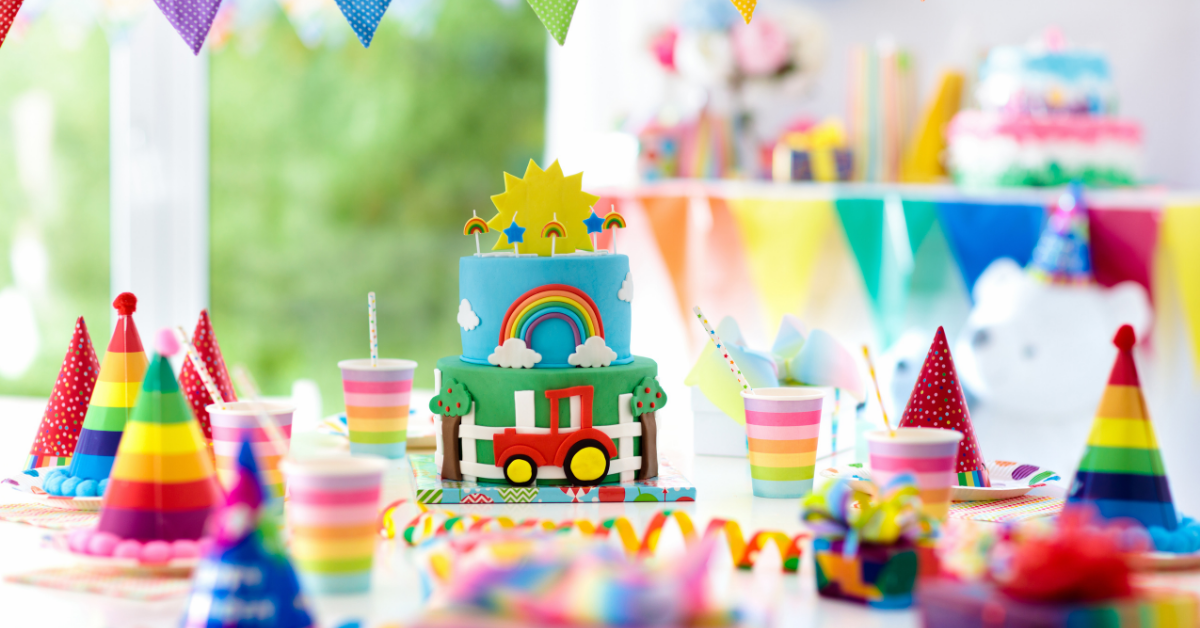kids birthday party table with hats, cake and decorations