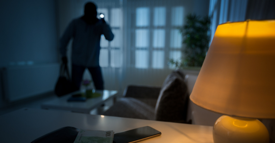 a thief breaking into a house at night