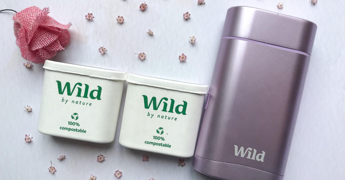 wild deodorant on a white background with small flowers placed around. 1 larger pink flower in top left corner