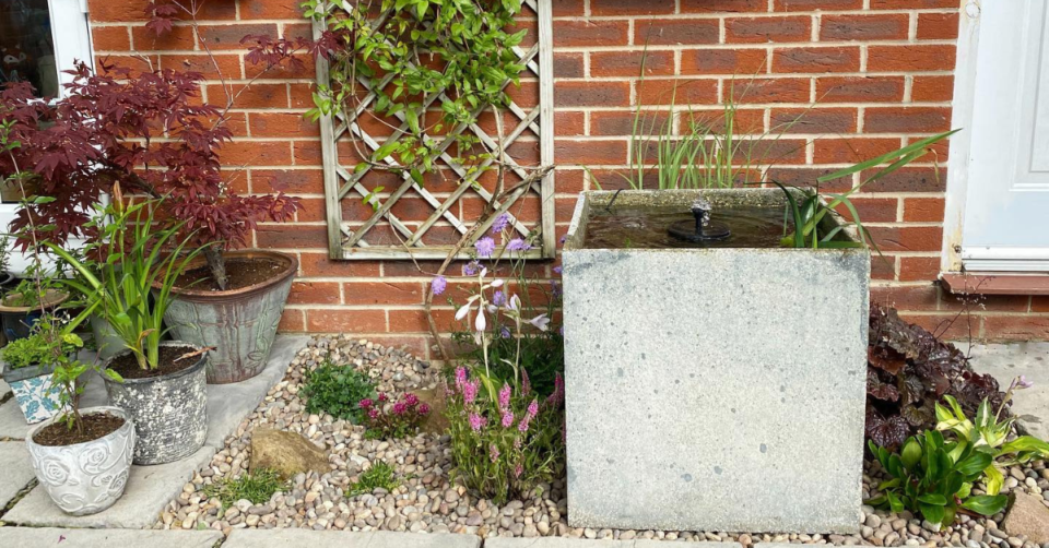 a pond made out of a planter surrounded by a rockery