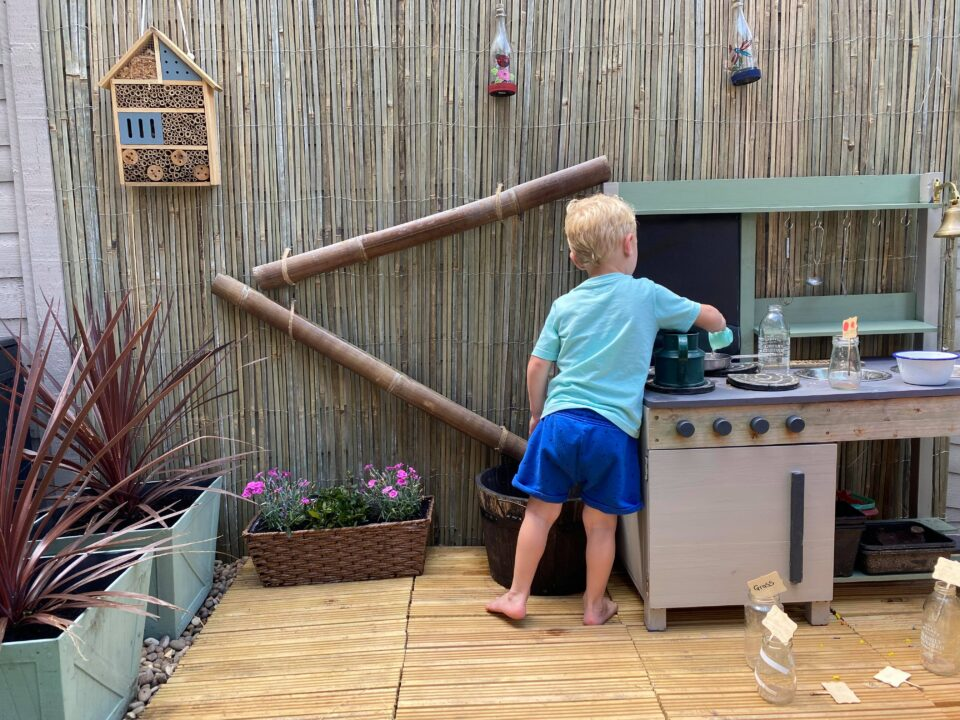 the completed mud kitchen with a child playing in it