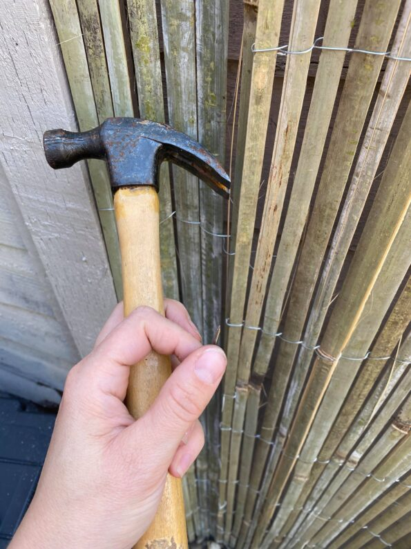 me holding a hammer and nail to tack the bamboo screening on
