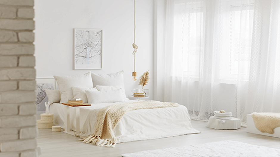 light and airy bedroom, very white with throws and cushions plus artwork