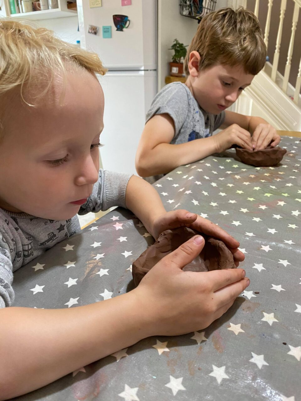 both boys making their clay hedgehogs at the kitchen table