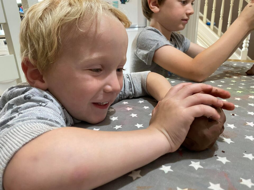 William smiling and making his clay hedgehog