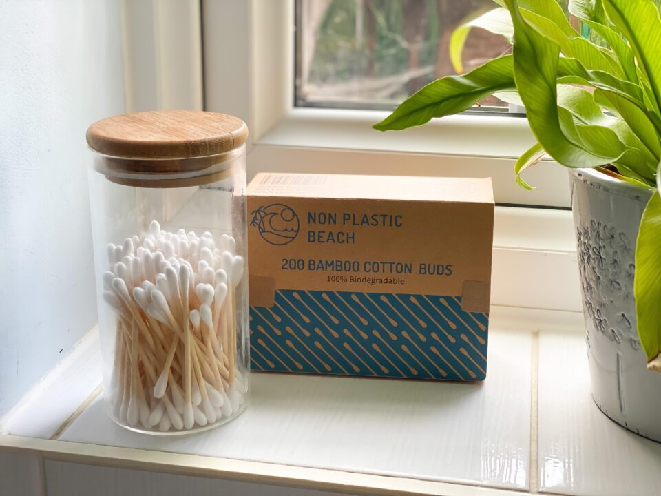 bamboo cotton buds on a window sill in a box with more in a reusable glass jar