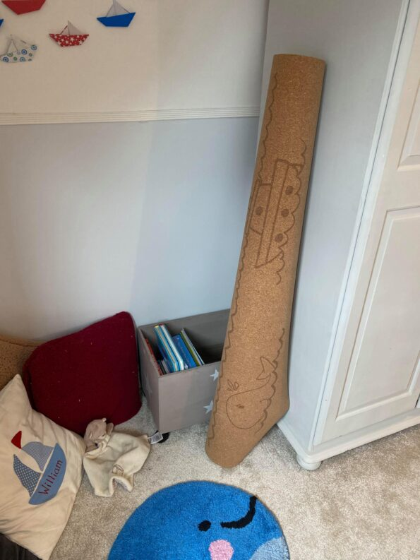 the mat rolled up and laying against the wardrobe next to his reading corner