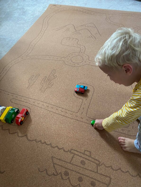 william playing with car toys on the Rocky Road Non-Toxic Play Mat