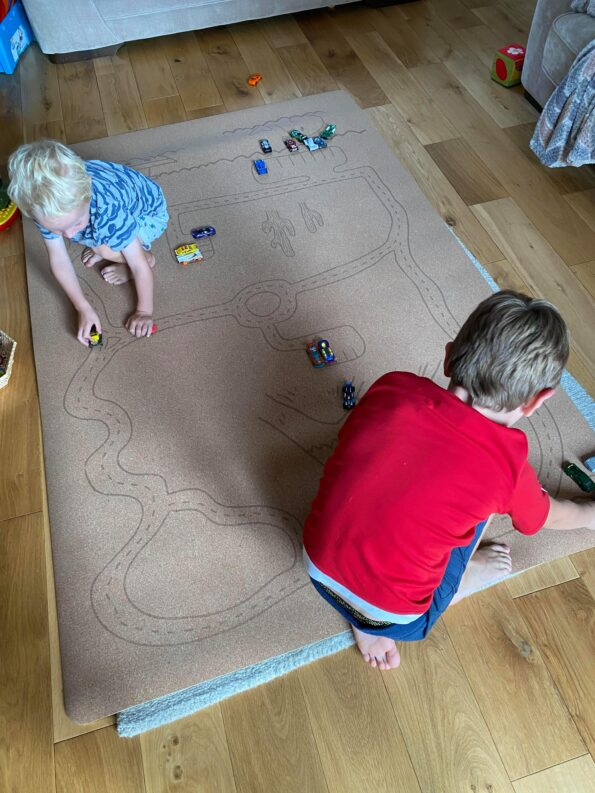 both boys playing with the play mat in the living room