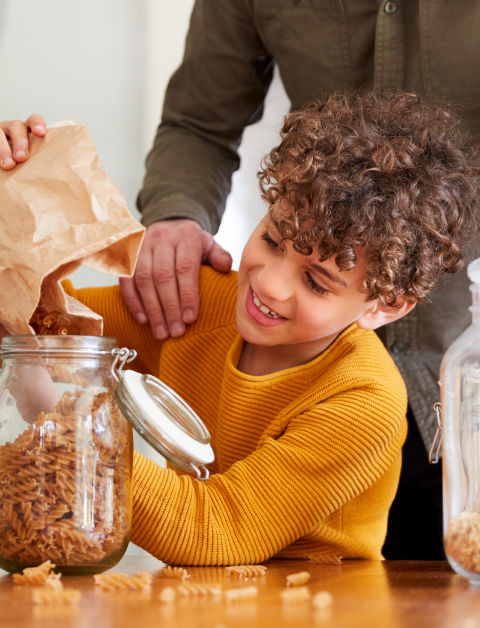 a child filling a jar with his dried food from a refill store