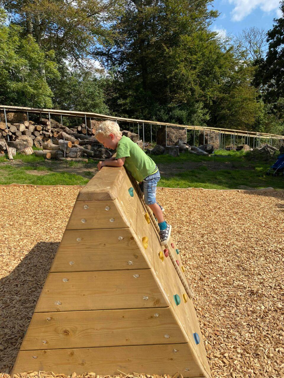 william climbing over a wooden climbing wall