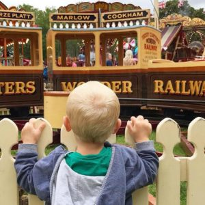 child looking over a fence at a train